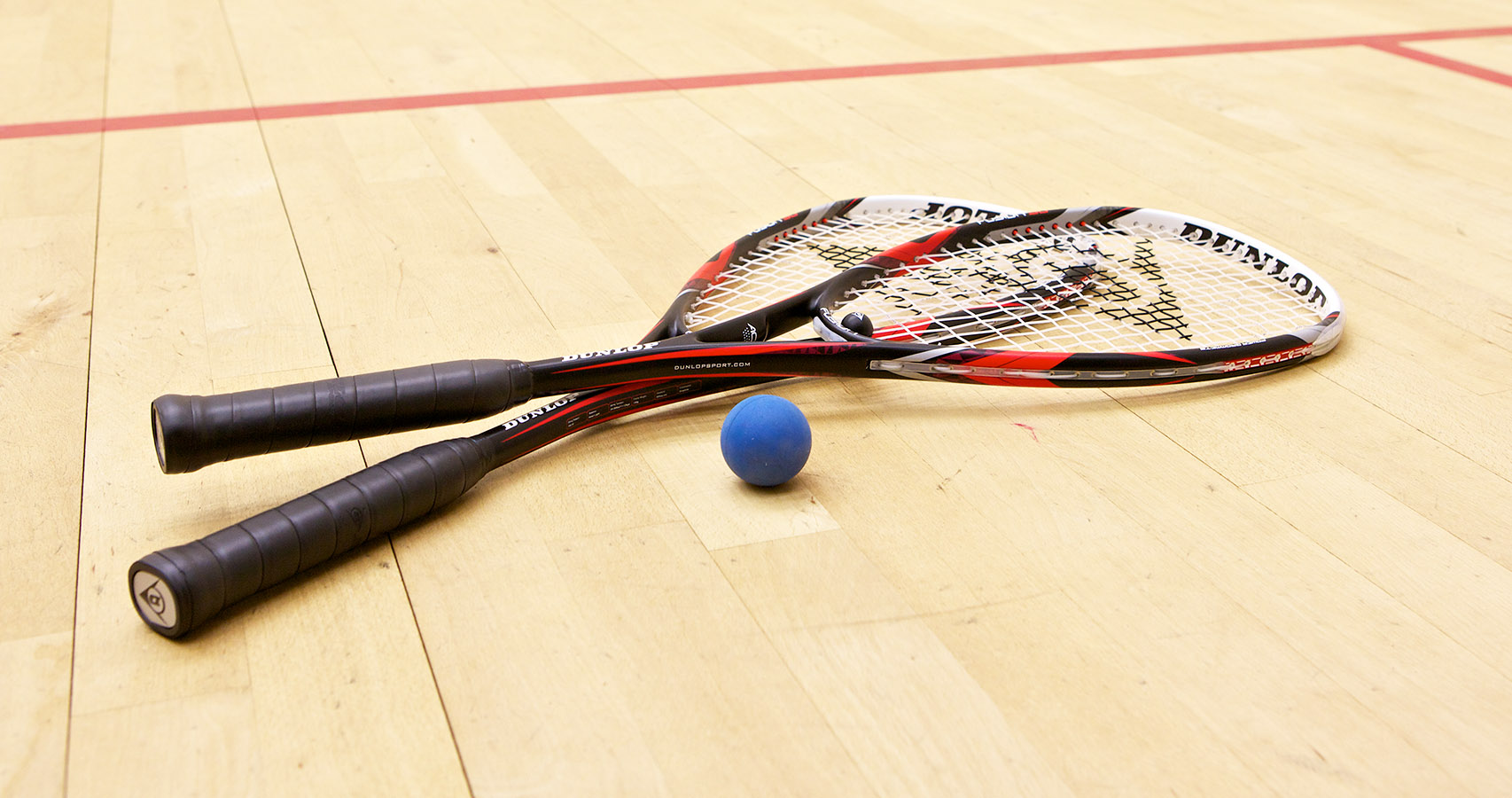 Two rackets on a squash court