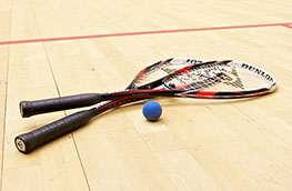 Squash rackets and ball on a squash court