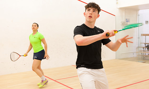 Young woman and man playing squash