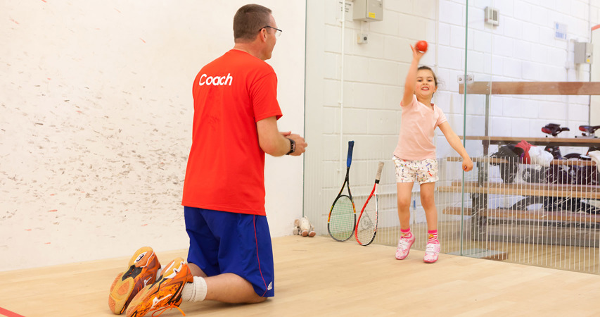 Coach with a young child playing squash
