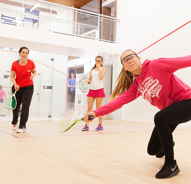 Female coach teaching young players on court
