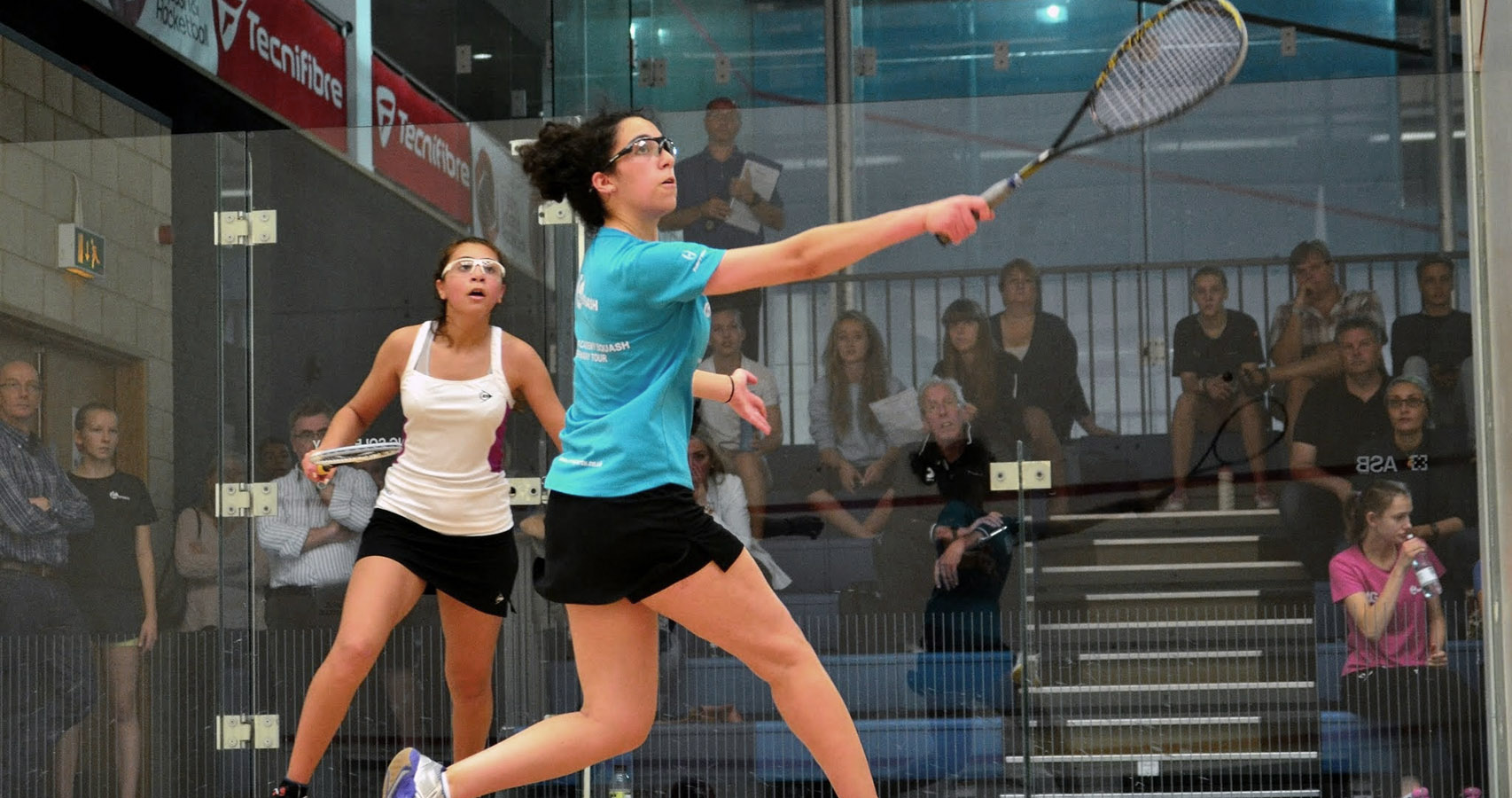 Two female squash players playing at the a county tournament