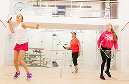 Three women playing squash