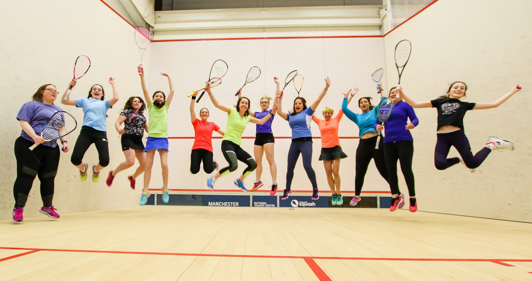 Group of female squash players jumping in the air