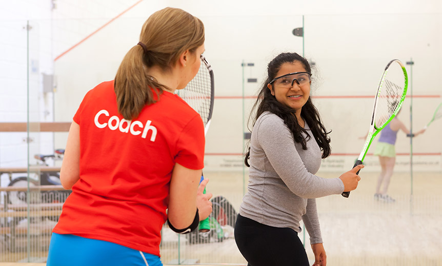 Female squash coach coaching a young teenager