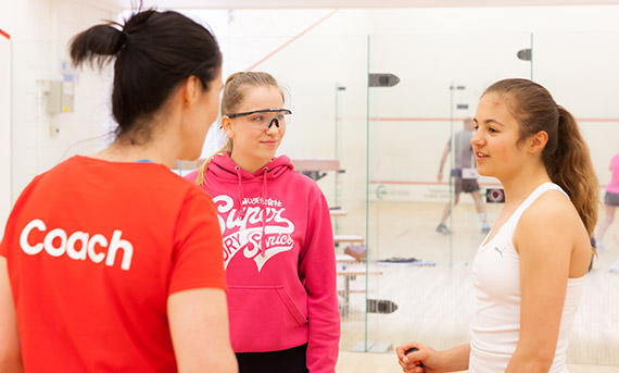 Squash coach with two young female players