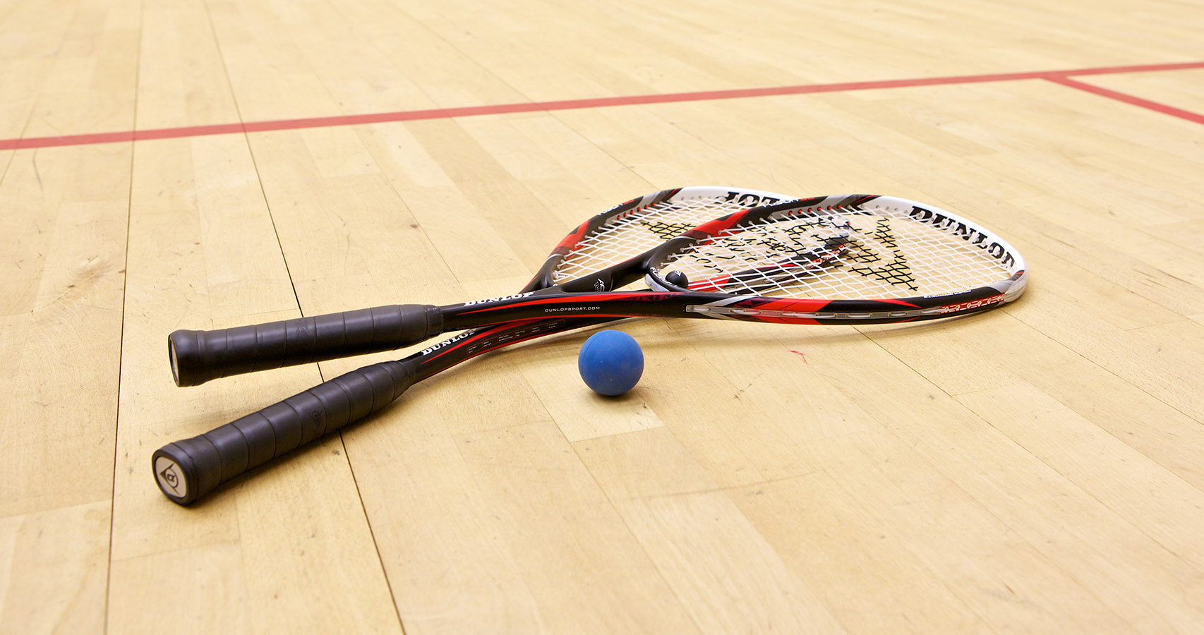 Two rackets and a squash ball on court