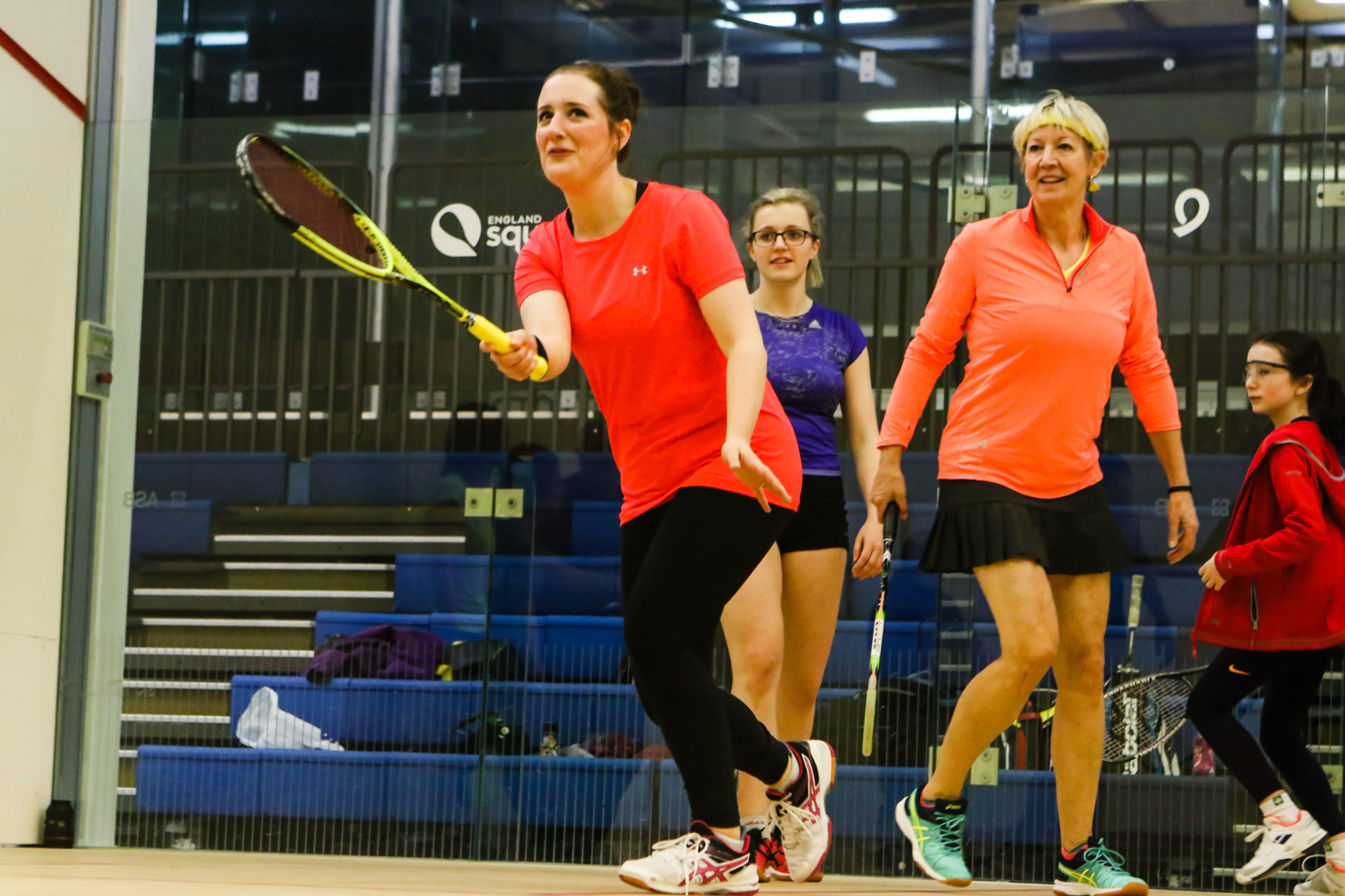 Squash girl hitting the ball