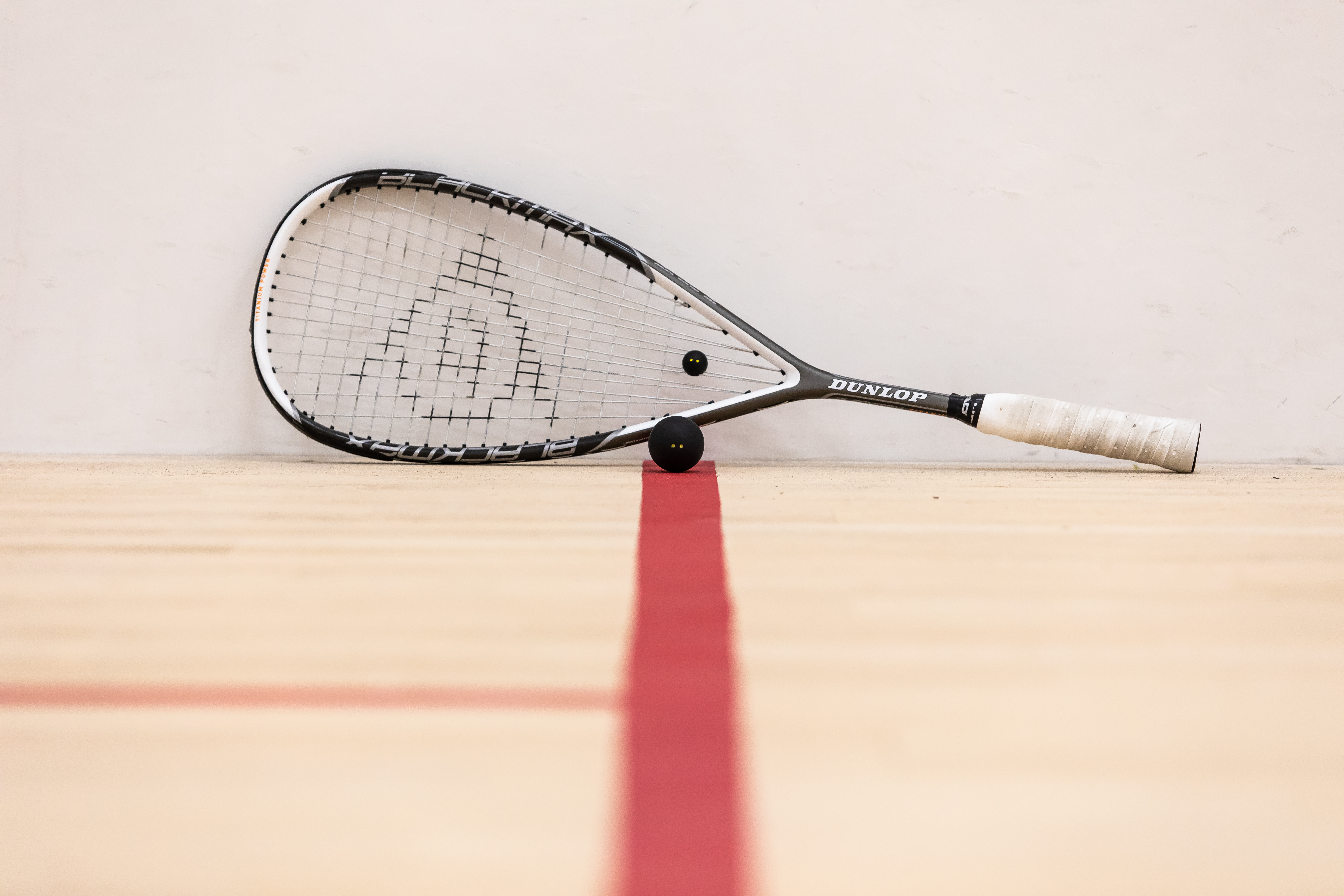 A squash racket and a ball on a court
