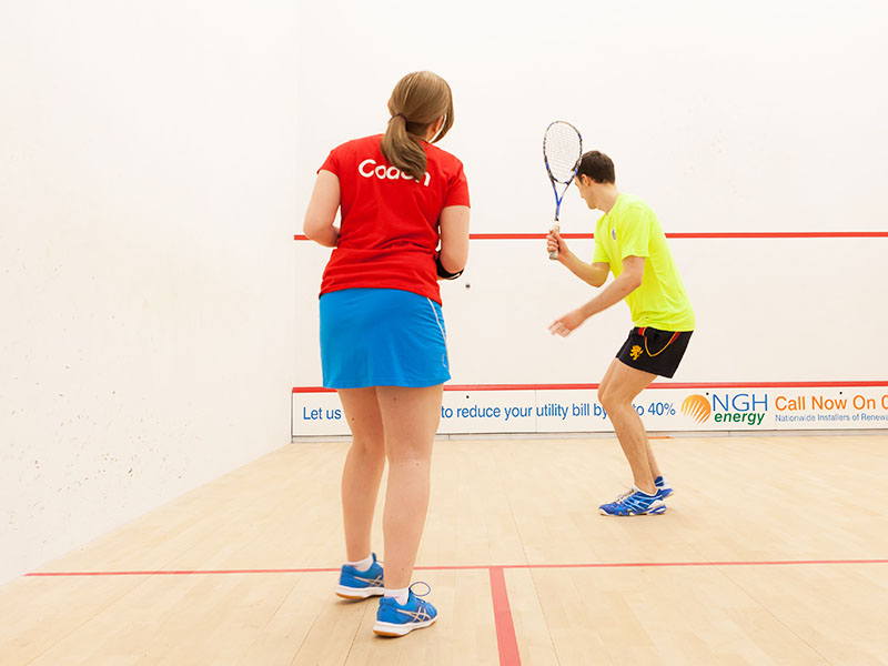 Female squash coach coaching a young male
