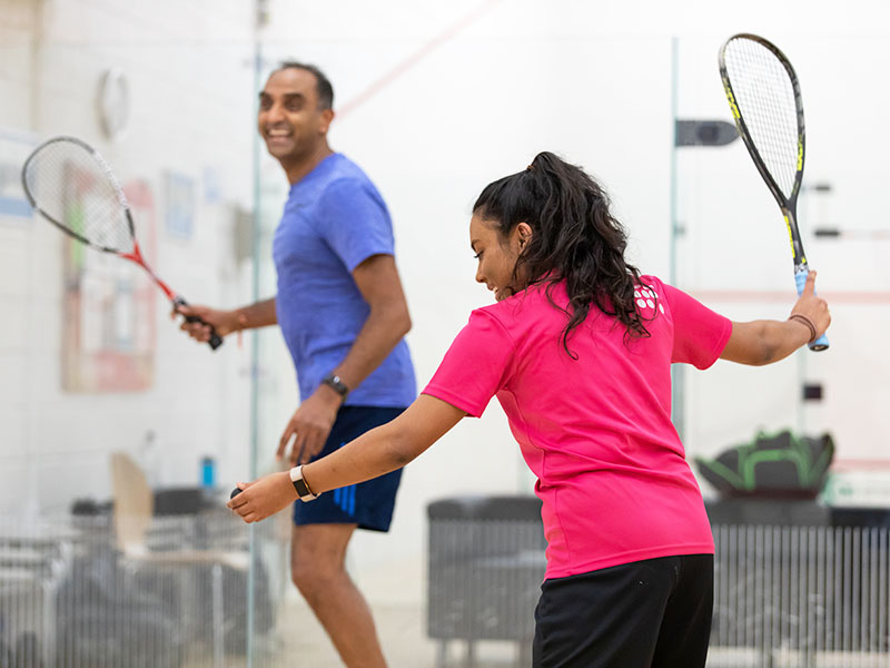 Man and woman playing squash