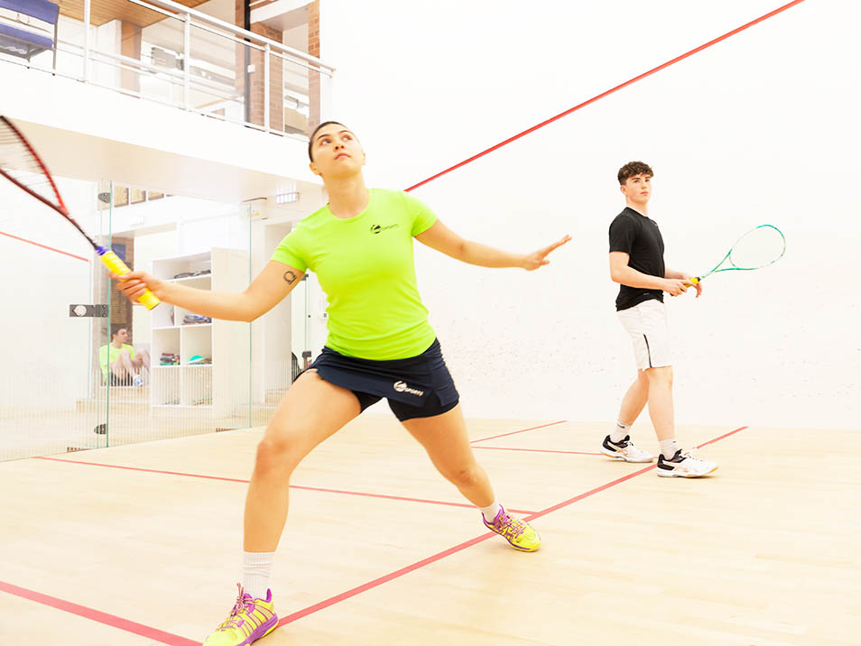 Woman and man playing squash