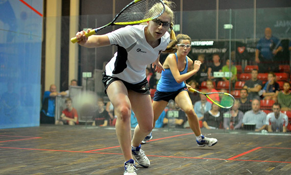 Two female squash players playing competitively