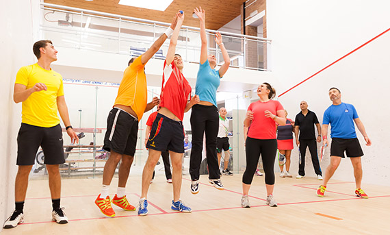 People participating in Squash 101 on a squash court