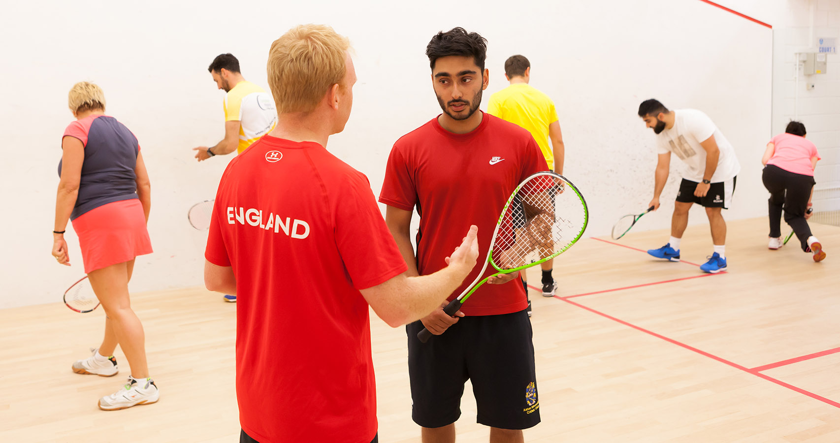 England coach tutoring a squash course