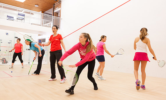 Women and girls playing Squash Girls Can on a court