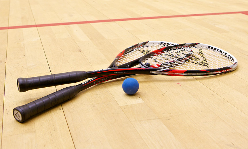 Two squash rackets and a ball on a court